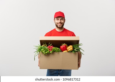Delivery Concept: Handsome Caucasian grocery delivery courier man in red uniform with grocery box with fresh fruit and vegetable