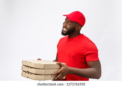 Delivery Concept - Portrait of Handsome African American Pizza delivery man. Isolated on Grey studio Background. Copy Space