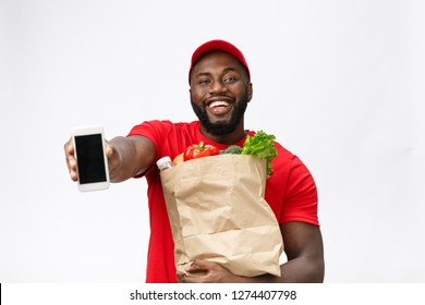 Delivery Concept - Portrait of Handsome African American delivery man or courier showing mobile phone on you to check the order. Isolated on Grey studio Background. Copy Space