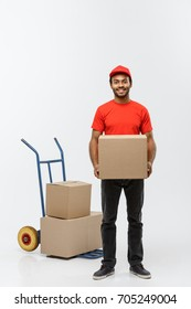 Delivery Concept - Portrait of Handsome African American delivery man or courier with hand truck and holding box. Isolated on Grey studio Background. Copy Space.