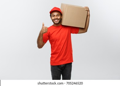 Delivery Concept - Portrait of Happy African American delivery man holding a box package and showing thumbs up. Isolated on Grey studio Background. Copy Space.