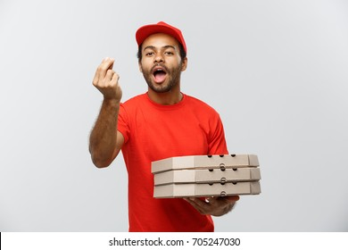 Delivery Concept - Portrait of Happy African American delivery man showing delicious gesture by hand with holding boxes of pizza package. Isolated on Grey studio Background. Copy Space.