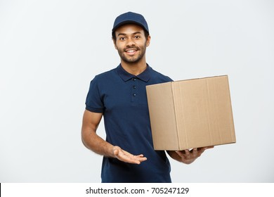 Delivery Concept - Portrait of Happy African American delivery man pointing hand to present a box package. Isolated on Grey studio Background. Copy Space.