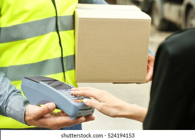 Delivery concept. Postman giving packages to woman, woman paying for service
