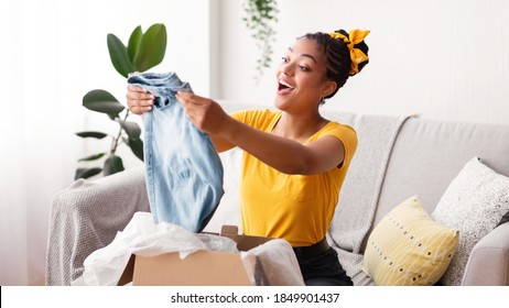 Delivery Concept. Smiling black woman holding new jeans, unboxing cardboard package, sitting on the couch in living room at home, free space. Excited lady happy with purchase and clothes shipment