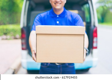 Delivery concept - Smiling happy young asian handsome male postal delivery courier man in front of cargo van delivering package holding box with service mind and blue uniform