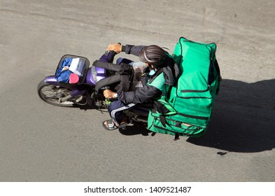 Delivery of consignments on motorbike. Motorcyclist rides with delivery in the many green bags on street Saigon city, Vietnam.