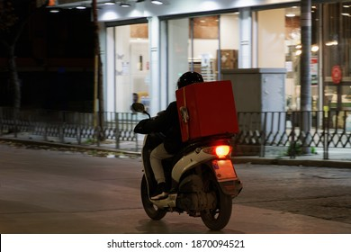 Delivery courier on unbranded motorbike speeding on city road at night. Illuminated view of male with helmet riding motorcycle to deliver take away food contained on a red box in Thessaloniki, Greece.