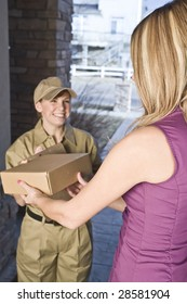 Delivery driver or courier handing package over to a woman