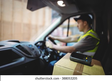 Delivery driver driving van with parcels on seat outside warehouse