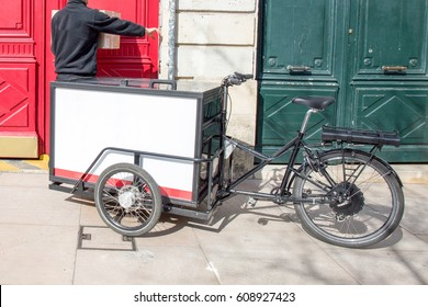 delivery driver with his or her trip bike delivers parcels to a customer
