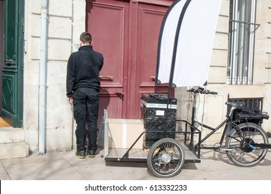 delivery driver rings at his customer house to deliver a parcel with his three-wheeled bicycle