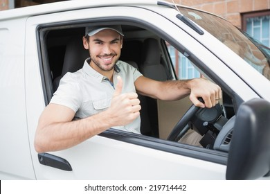Delivery driver showing thumbs up driving his van outside the warehouse