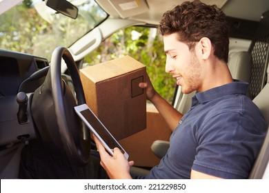 Delivery Driver Sitting In Van Using Digital Tablet