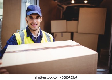 Delivery driver smiling at camera by his van holding parcel outside the warehouse