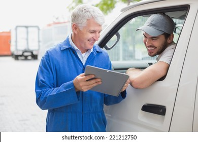 Delivery driver smiling at camera with customer outside the warehouse