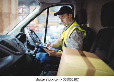 Delivery driver using tablet in van with parcels on seat outside warehouse