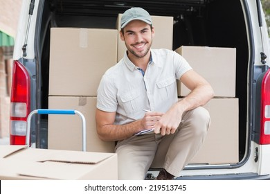 Delivery driver writing in clipboard outside the warehouse