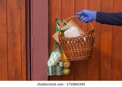 Delivery during quarantine. A delivery service employee delivers a bag and basket of food and hygiene products. Help with quarantine due to coronavirus infection Covid-19