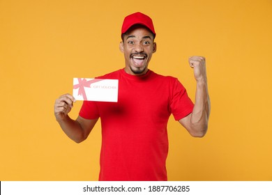 Delivery employee african man 20s in red cap blank print t-shirt uniform workwear work courier dealer service concept hold mockup gift certificate voucher coupon isolated on yellow background studio