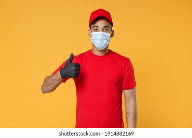 Delivery employee african man in red cap blank print t-shirt face mask gloves uniform work courier dealer service on quarantine coronavirus covid-19 virus concept isolated on yellow background studio