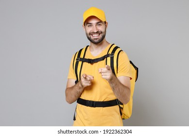 Delivery employee man guy male 20s in yellow cap t-shirt uniform thermal food bag backpack work courier service during quarantine coronavirus covid-19 virus, posing isolated on gray background studio