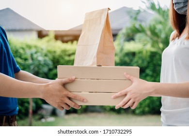Delivery express of asian woman picking food social distancing wearing mask protection,prevention infection risk customer receiver shipping deliver shopping online while quarantine at front home.