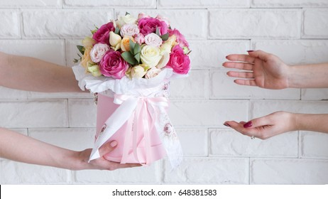 Delivery of a floral workshop. The customer receives his order-a bouquet of pink and pale yellow roses. Hand courier pass flowers to the buyer