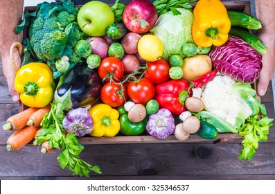 Delivery of fresh organic vegetables in wooden box, local market food.Hands holding box with vegetables and fruits.