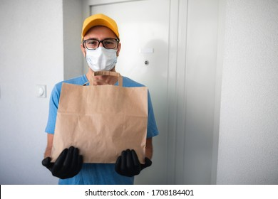 Delivery guy with protective mask holding box / bag with groceries and POS for contactless payment.