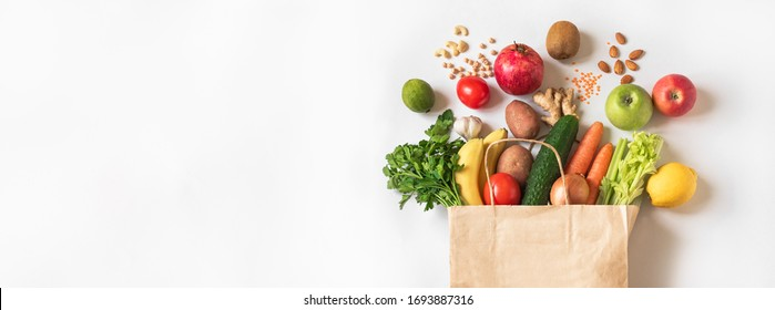 Delivery healthy food background. Vegan vegetarian food in paper bag vegetables and fruits, nuts and grains on white, copy space, banner.Grocery shopping food supermarket and clean eating concept. - Shutterstock ID 1693887316