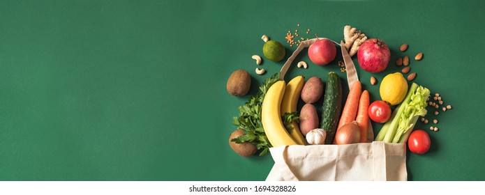 Delivery healthy food background. Vegan vegetarian food in eco bag vegetables and fruits, nuts and grains on white, copy space, banner.Grocery shopping food supermarket and clean eating concept.