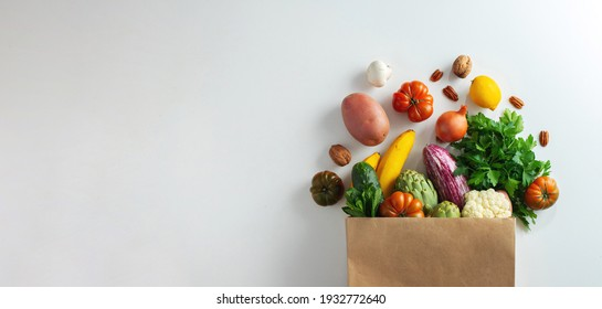 Delivery healthy food background. Healthy vegan vegetarian food in paper bag vegetables and fruits on white, copy space, banner. Shopping food supermarket and clean vegan eating concept