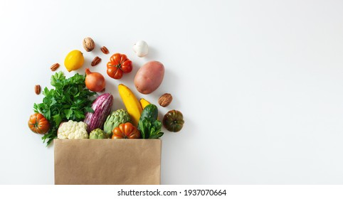 Delivery healthy food background. Healthy vegan vegetarian food in paper bag vegetables and fruits on white, copy space, banner. Shopping food supermarket and clean vegan eating concept.