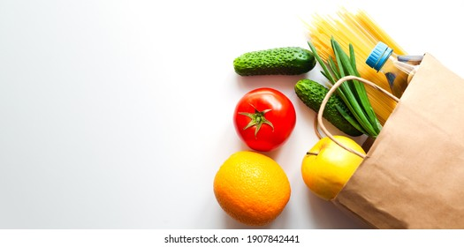 Delivery healthy food. Fresh vegetables and fruits in paper shopping bag on the table. Top view. Copy space. Banner.