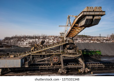 delivery of iron ore by a conveyor belt from a warehouse and loading into railway dump cars. Mining iron ore mining.