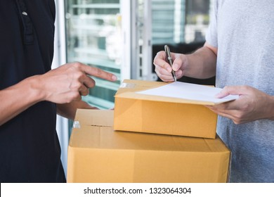 Delivery mail man giving parcel box to recipient, Young man signing receipt of delivery package from post shipment courier at home.