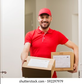 delivery, mail, people and shipment concept - happy man in red uniform with parcel boxes at open customer door