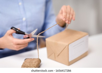 delivery, mail service, people and shipment concept - close up of woman packing parcel box and cutting rope with scissors at post office