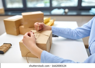 delivery, mail service, people and shipment concept - close up of woman packing eco parcel box and tying rope at post office