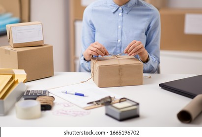 delivery, mail service, people and shipment concept - close up of woman packing parcel box and tying rope at post office