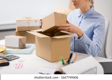 delivery, mail service, people and shipment concept - close up of woman packing parcel box at post office