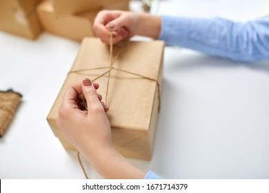 delivery, mail service, people and shipment concept - close up of female hands packing eco parcel box and tying rope at post office