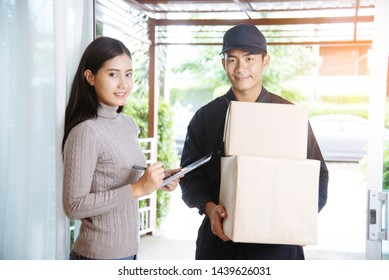 Delivery mail shipping package services . Young deliveryman in uniform shipping goods package to recipient from shopping online and signing for got parcel package service on clipboard.