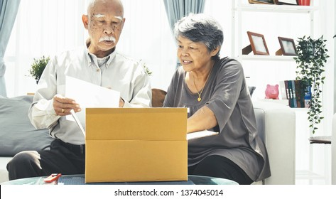 Delivery, mail, shipping and people concept - senior man and woman opening parcel box at home,
