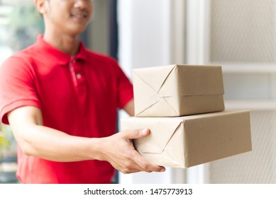 Delivery and mailing service concept. Smiling Asian postman in red uniform and cap delivering small and medium size of post boxes at the door waiting customer come to get it.