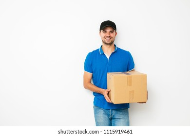 delivery man in blue shirt standing politely with his package, cardbox, in hands on wite background