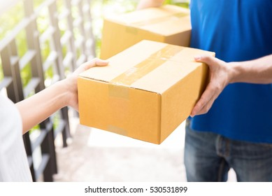 Delivery man in blue uniform handing parcel box to recipient - courier service concept