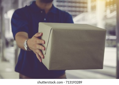 Delivery man in blue uniform holding a cardboard box while standing in public city.