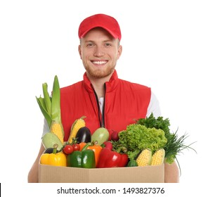 Delivery man with box of fresh vegetables on white background